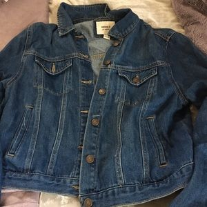 Blue Jean jacket with rip in sleeve.